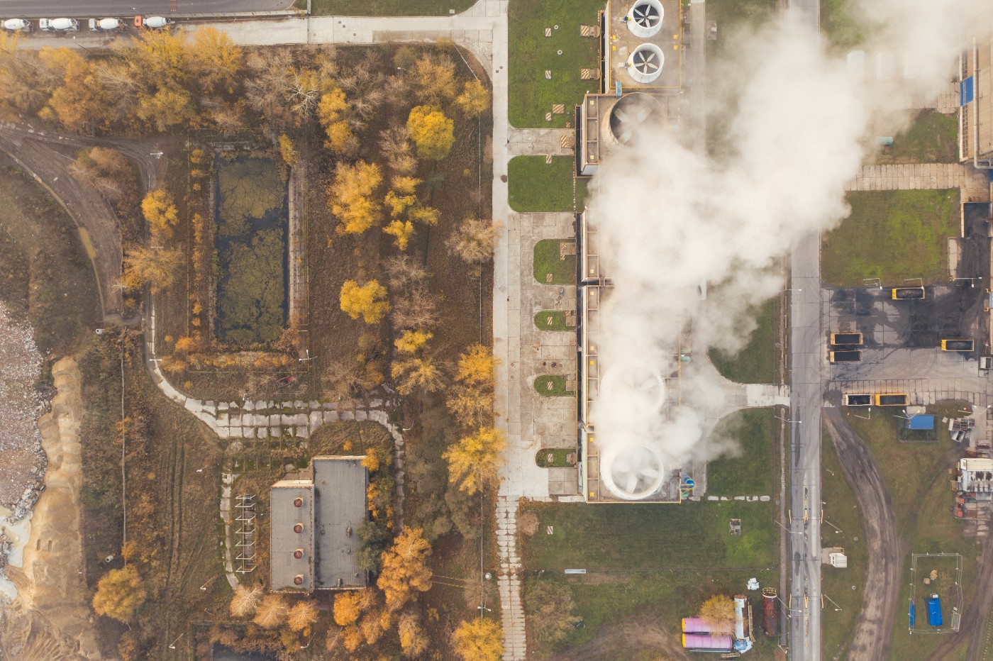 A bird's eye view of a large factory area with white smoke coming out of the chimneys.