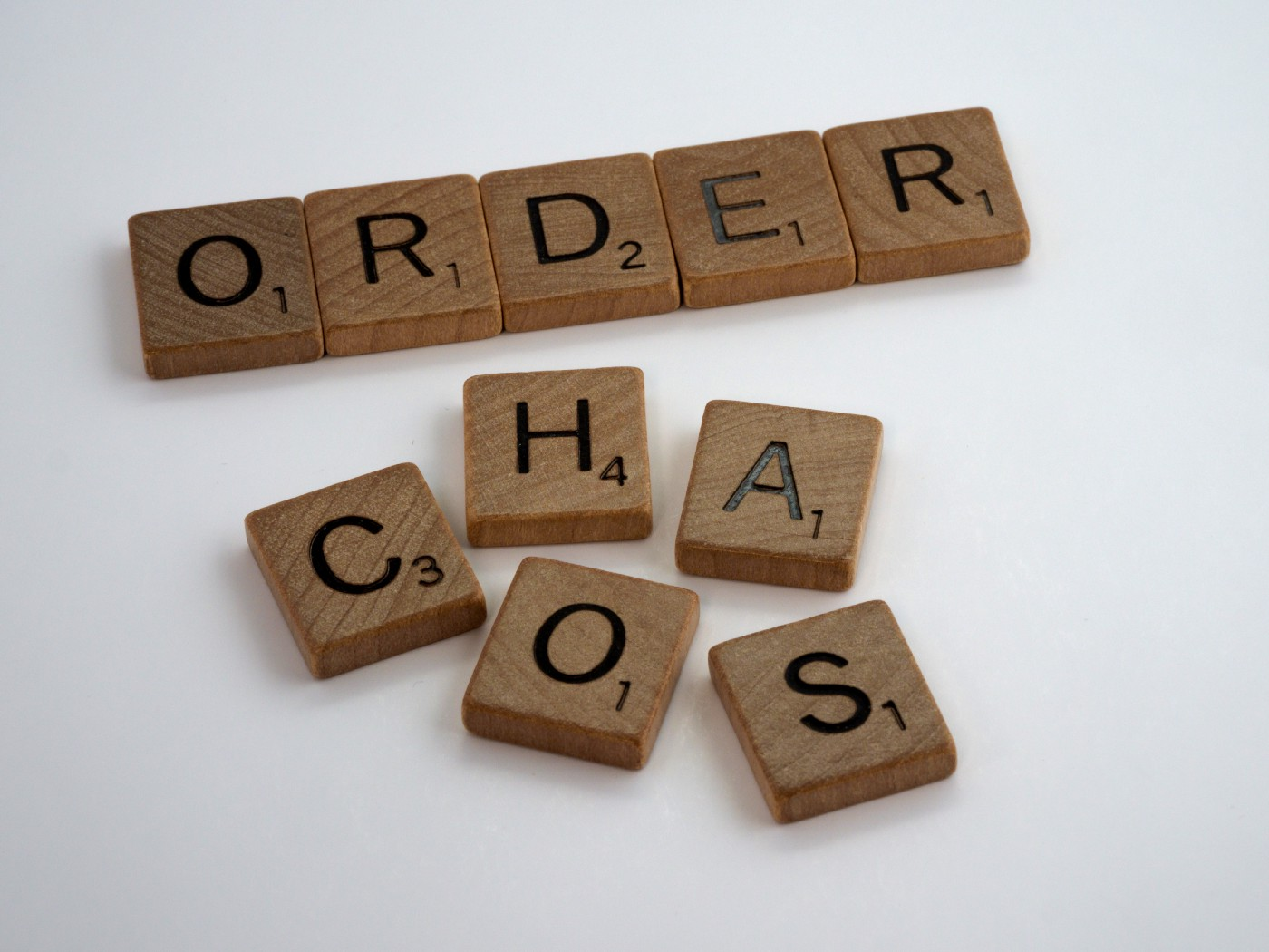 By Brett Jordan—order and chaos spelled in scrabble tiles; photo on Dr. James Goydos 2021 article about prison