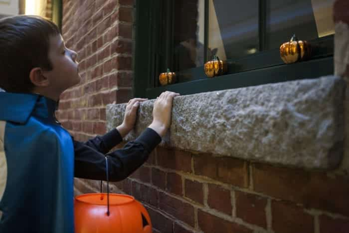 Young boy wearing a cape, holding a jack-o-lantern candy bucket, looking in a window with halloween decorations