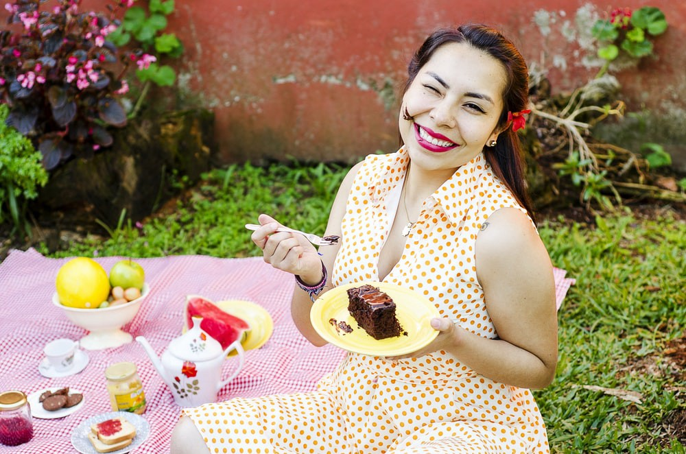 Image of a lady eating Chocolate cake smeared on her face, but she is happy and content