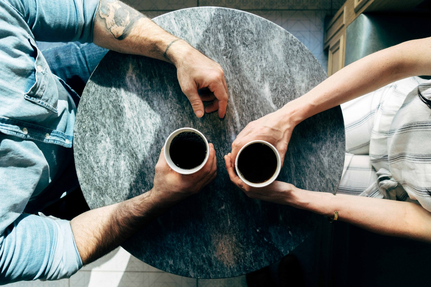 Two people each with a cup of coffee in their hand sitting at a round table.