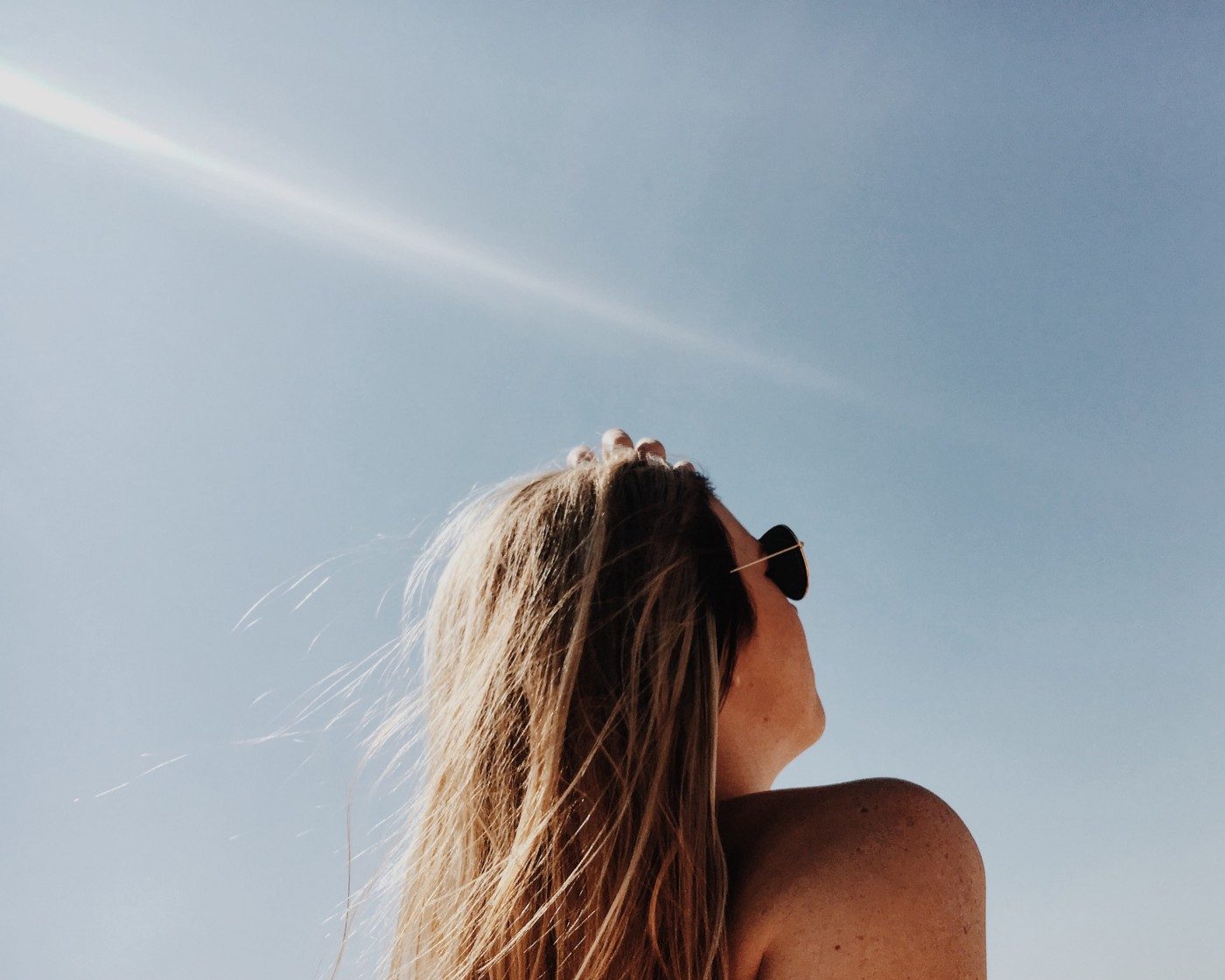 a woman standing outside looking up at the sky with sunglasses on