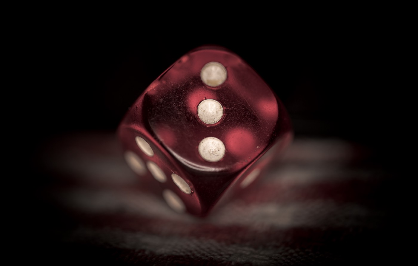 A red die being rolled and showing three dots in front of a black background