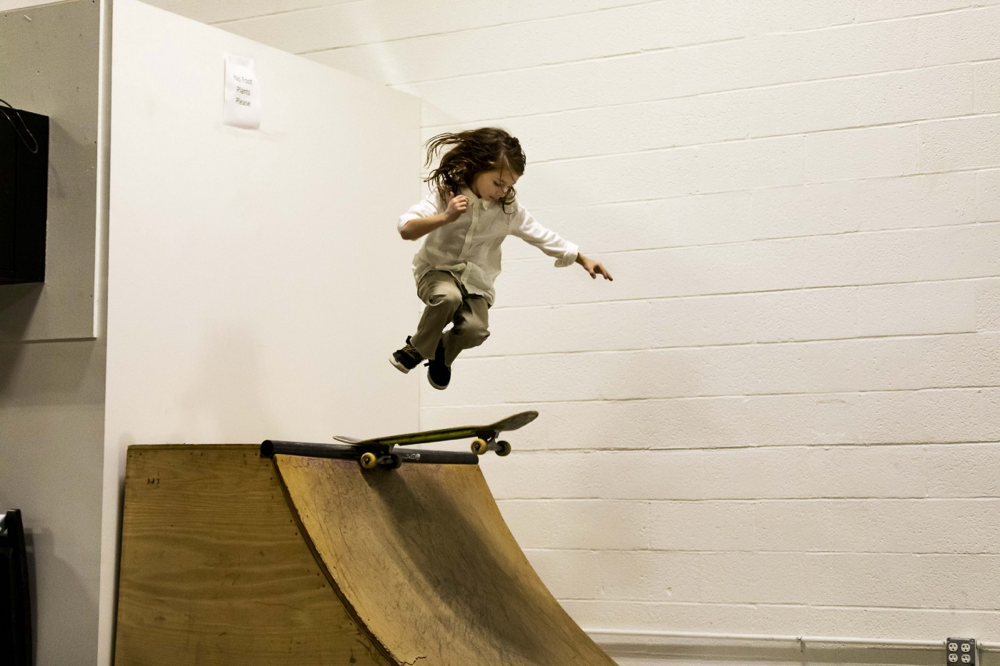 A photo of a young girl skateboarding on a ramp.