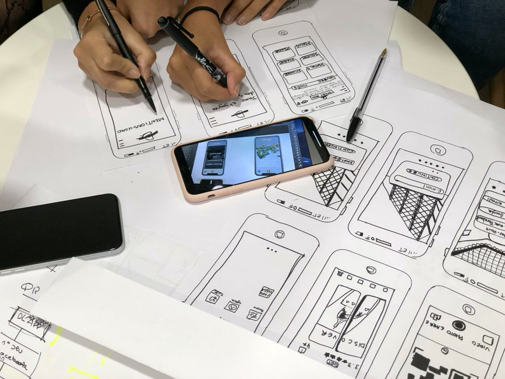 People sketch phone interfaces on a table together