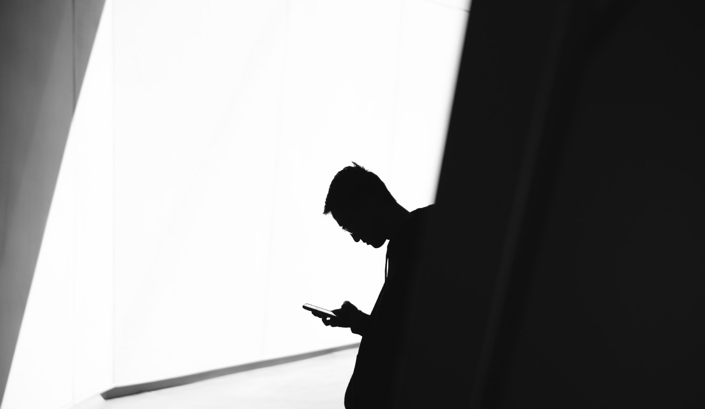 Black and white photo of man on phone discovering the secret to great writing.