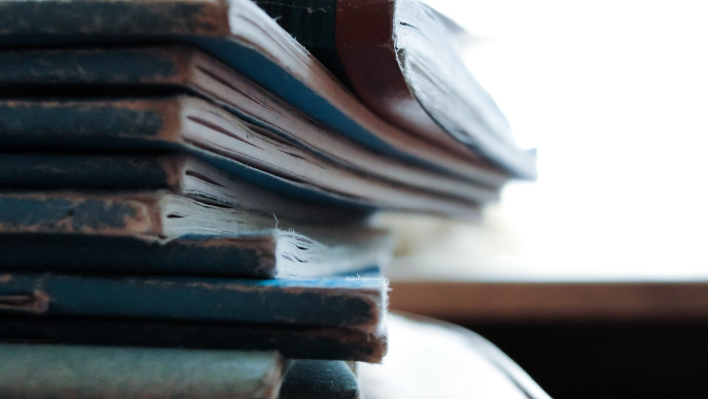a stack of old worn out paper journals