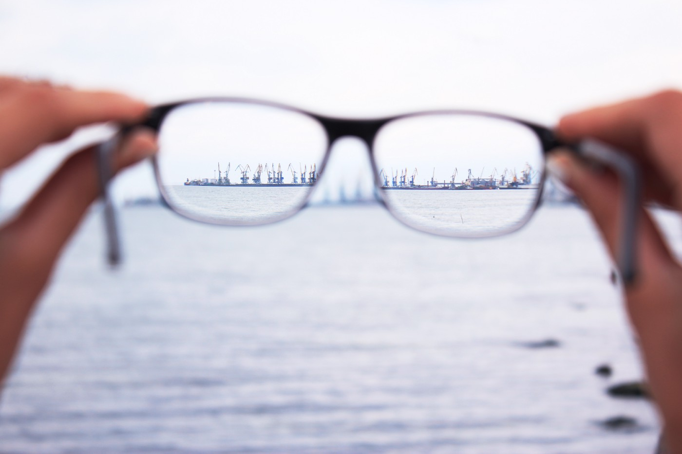 A pair of glasses in the foreground focus to reveal machinery in the ocean in the background