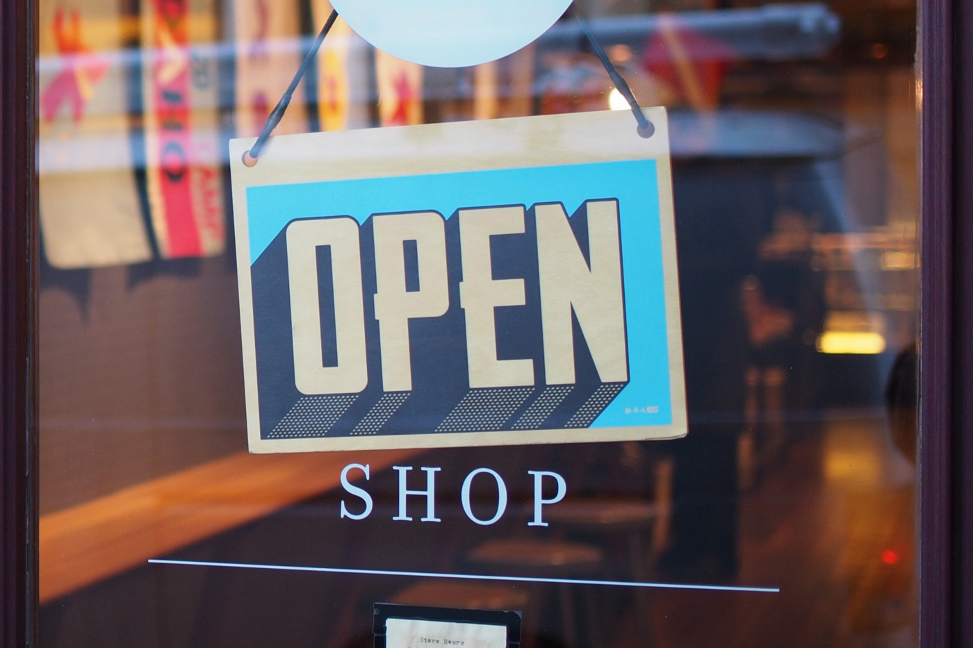 A blue and white OPEN sign hanging on the inside of a glass door above the word SHOP.