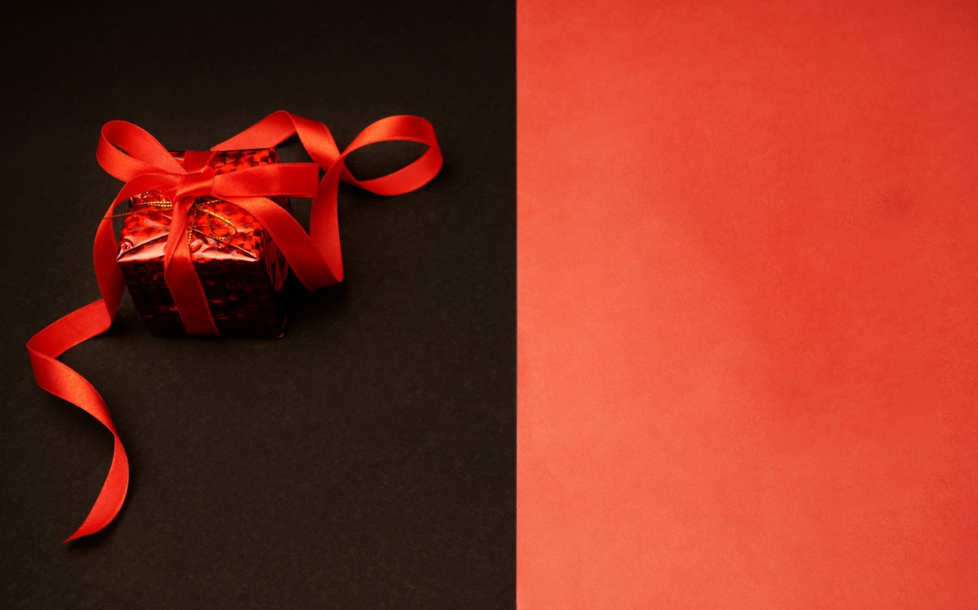 gift box wrapped in red paper with a red ribbon