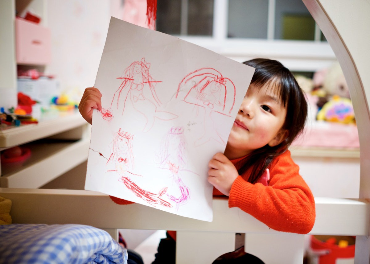 young Asian girl holding up a crayon picture she drew of several mermaids