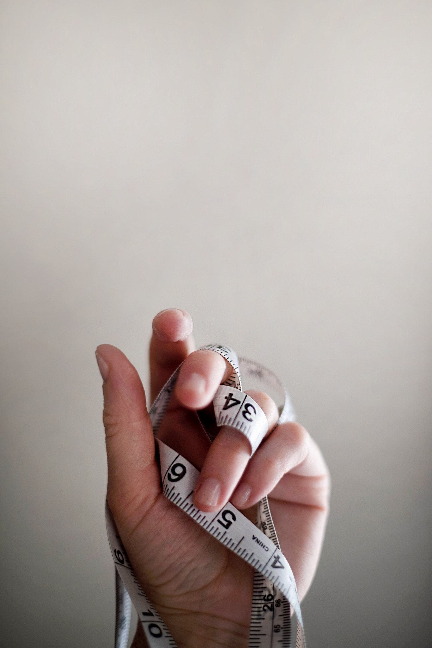A person's hand holding an etnangled measuring tape in a close up.
