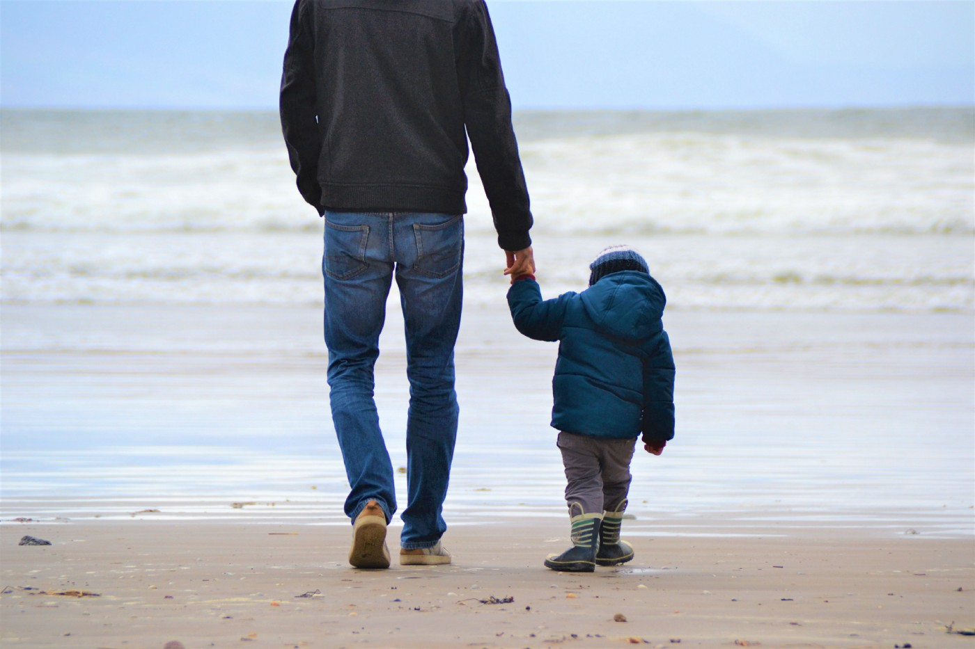 a dad walking hand-in-hand with his son along a beach with waves crashing the shoreline.