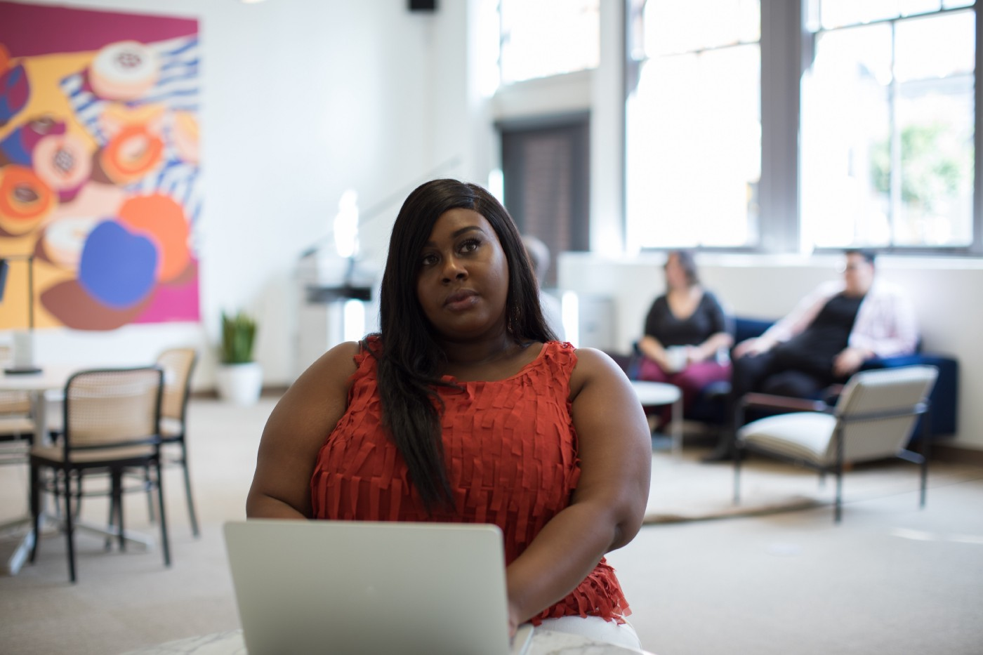 Black woman in red top sitting on her own while white co-workers are together in the background, racism, race, whiteness, white supremacy, black, inequality, injustice, white, systemic racism