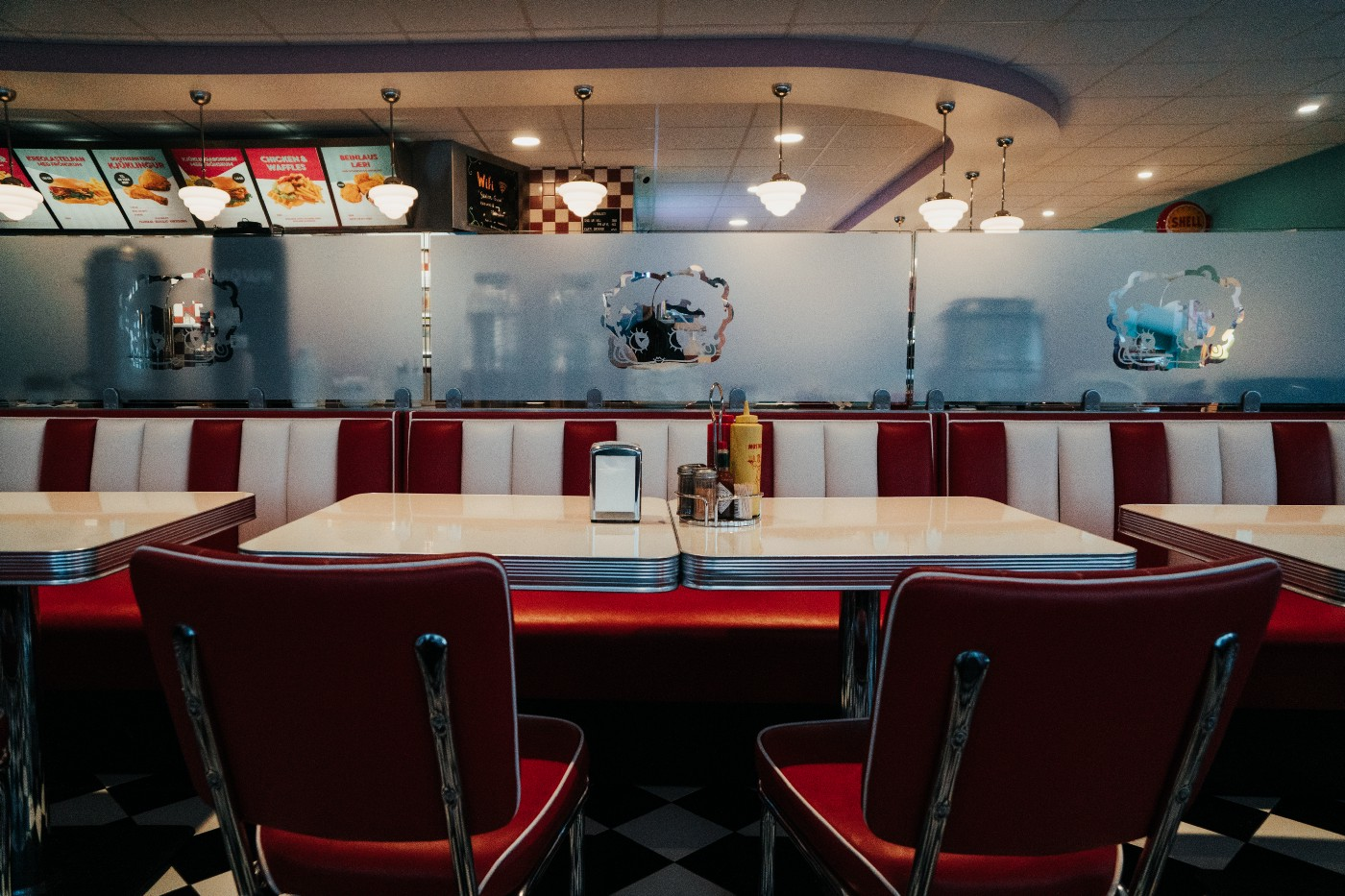an empty booth at an old-school diner with condiments and a napkin dispenser