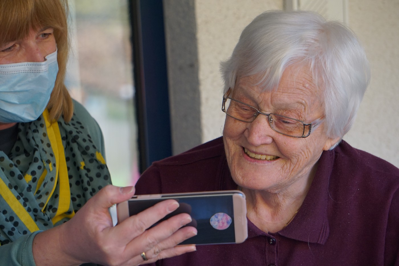 elderly woman smiles while looking at phone held by another woman wearing a mask
