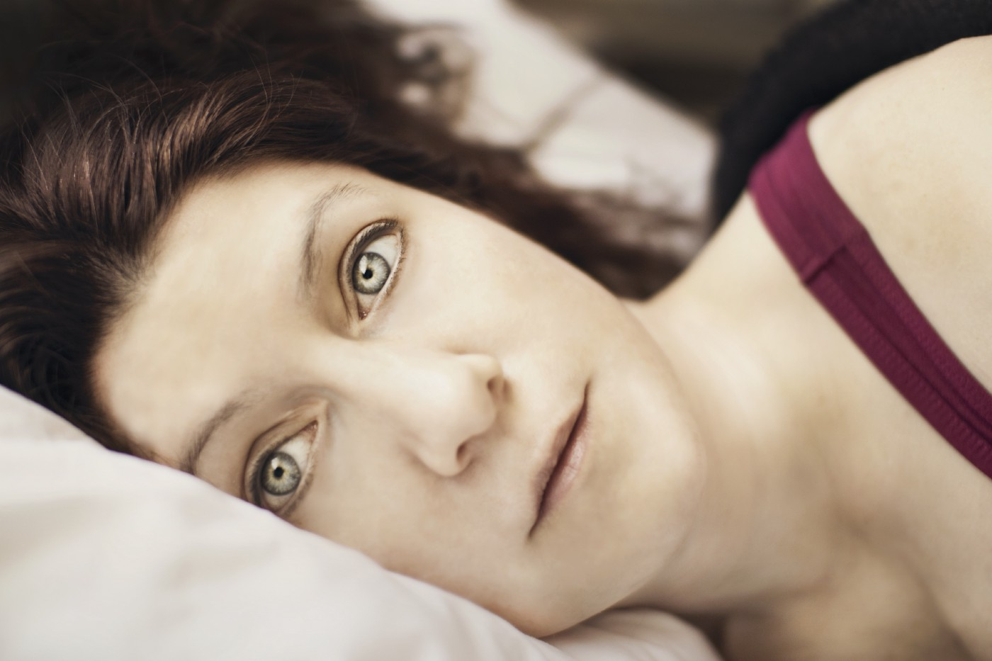 Woman lying on her side in bed staring into space.