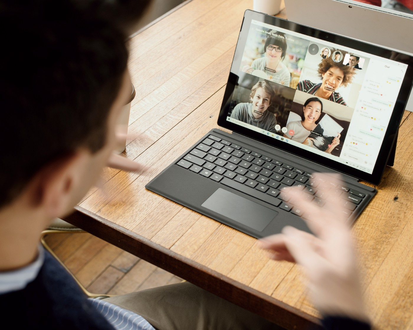 A man talks to others through his laptop on a video call.