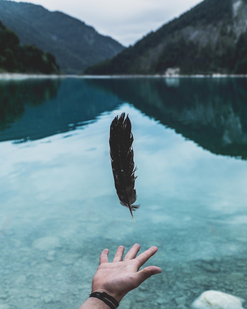 A feather being released by a hand into a water body surrounded by mountains.