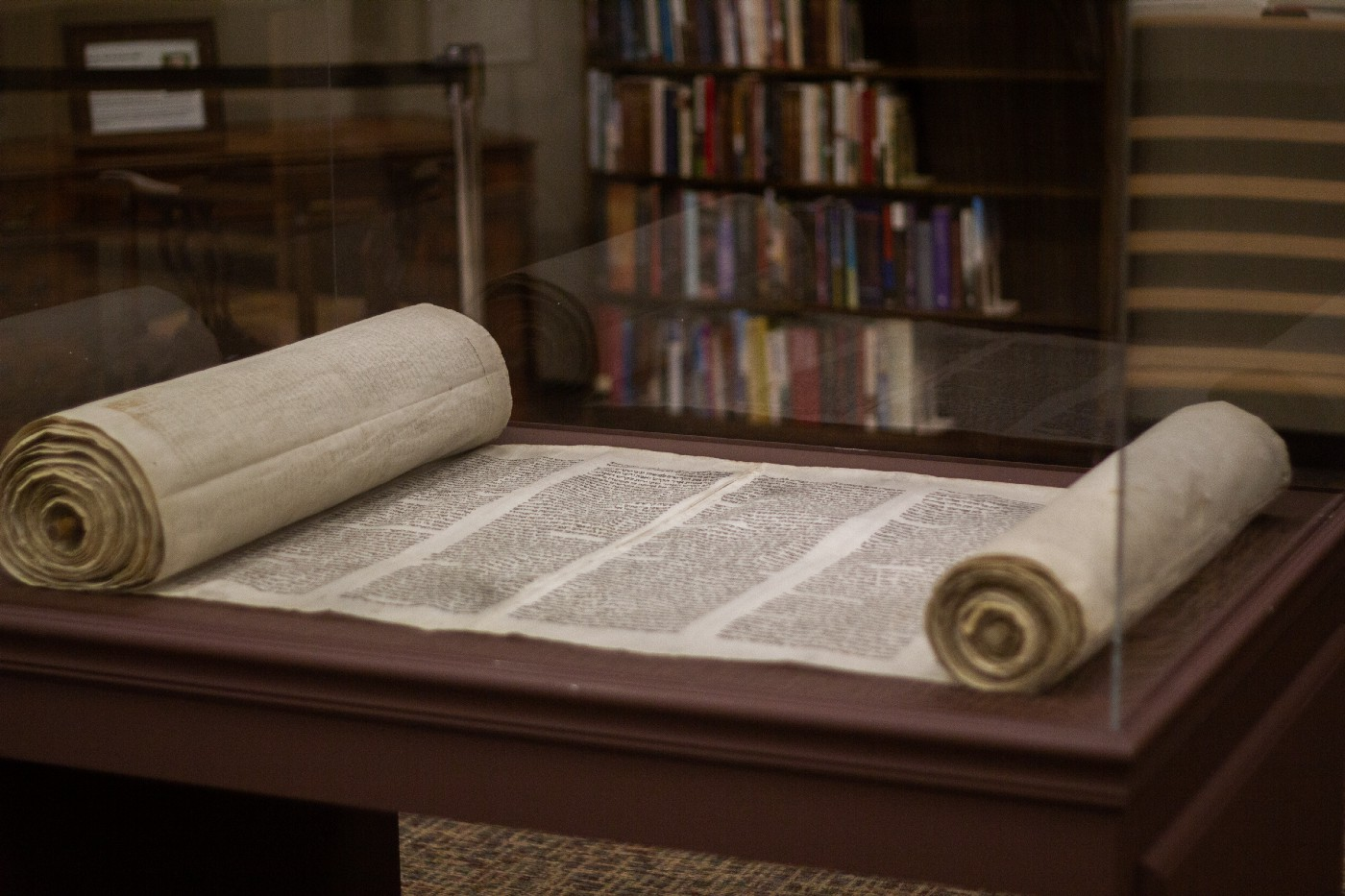 A scroll in a display case on a table