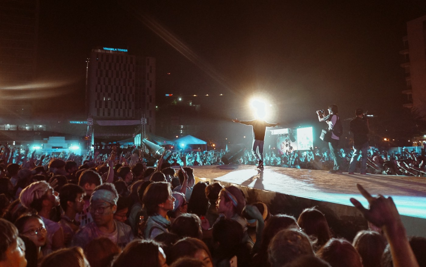 There is a spherical halo obliterating the head of a rock star on a cat walk. A crowd surrounds the protruding stage.