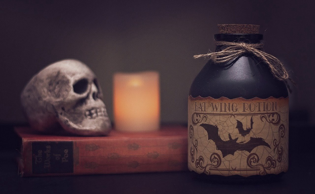 Spooky picture of a skull, candle, and potion bottle.