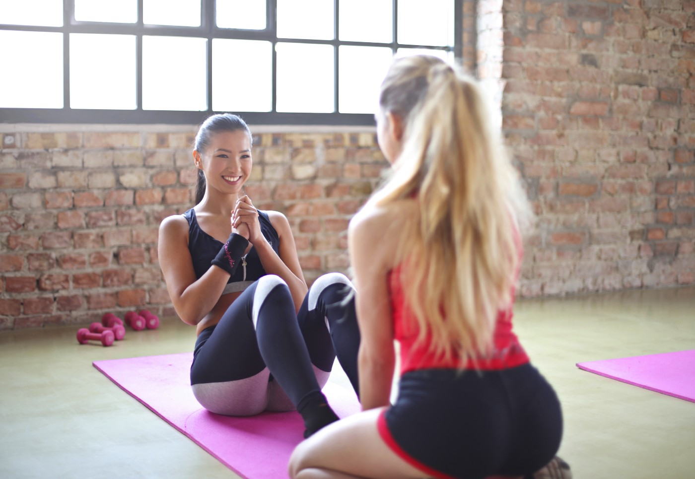 Two women working out with one person doing sit ups on a yoga mat