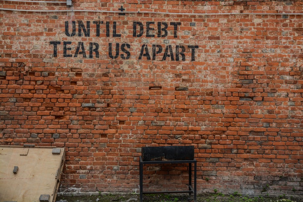 "A wall which says ""Until debt tear us apart"""