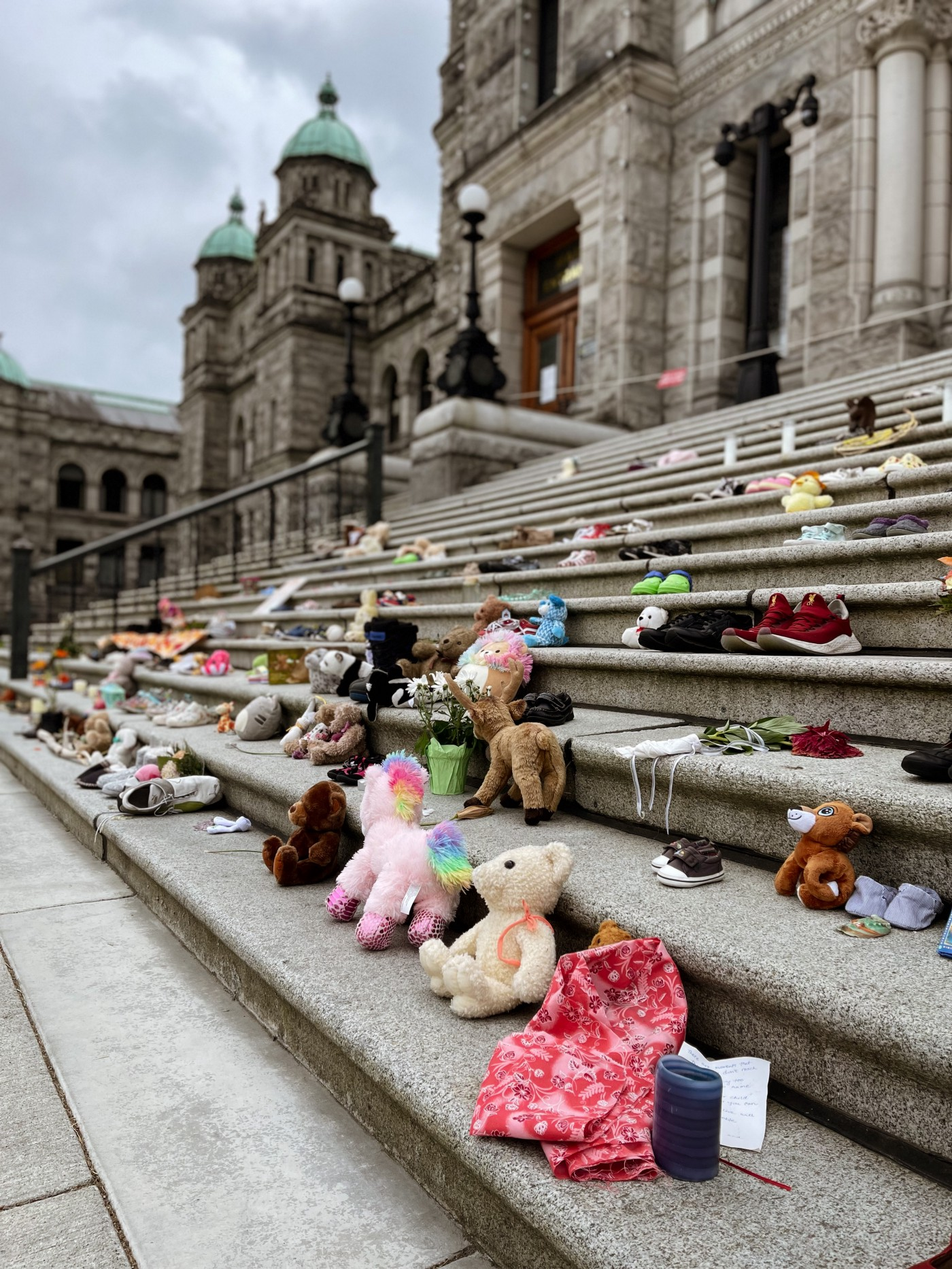 Children's shoes and stuffed toys line the stairs of a church.