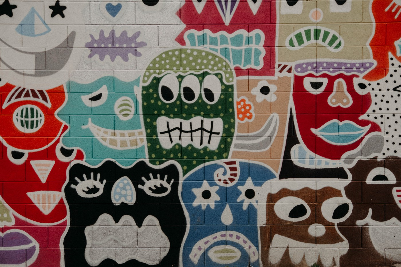 wall covered in graffiti of unusual faces