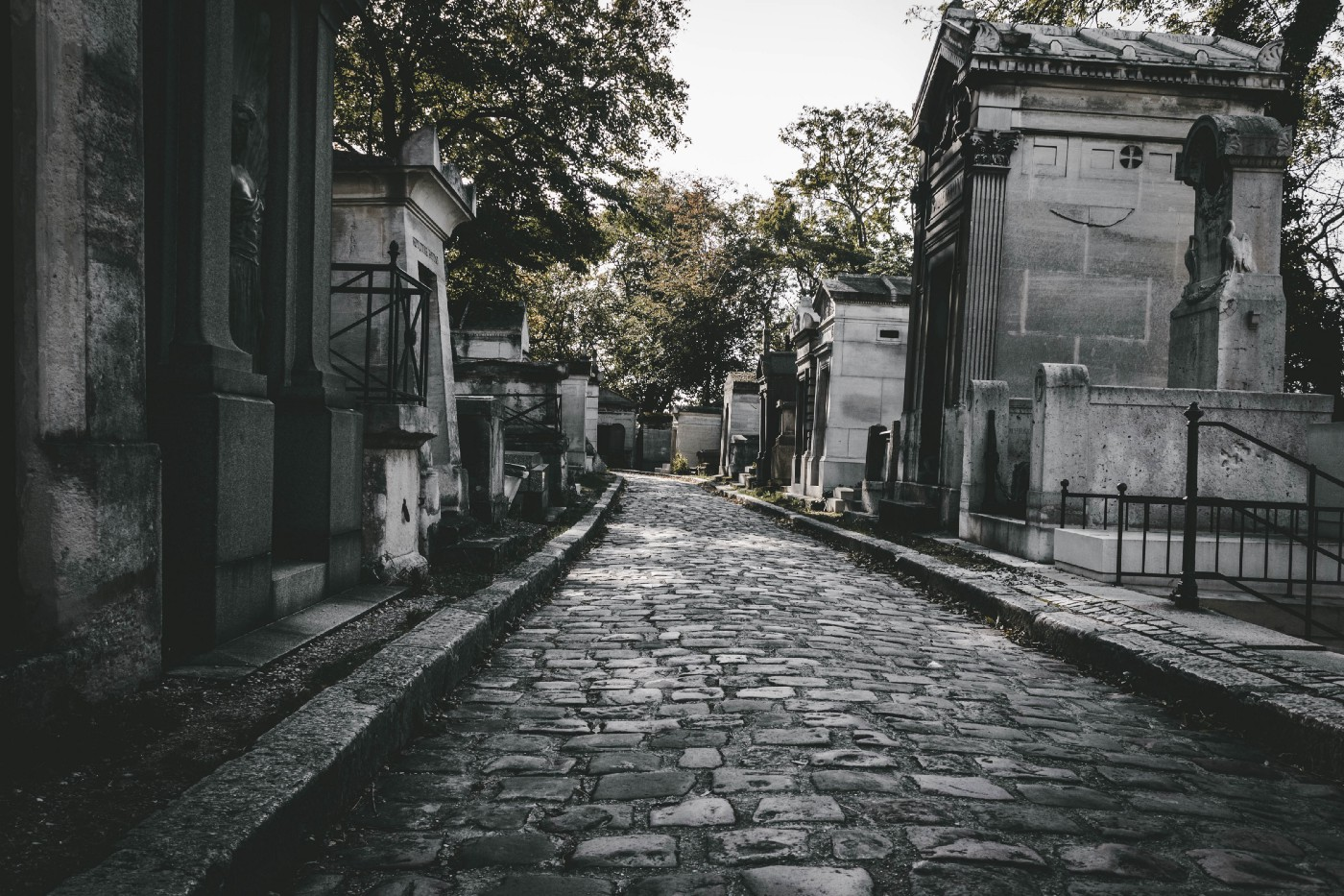 A darkish image of a cobblestone path to a graveyard.
