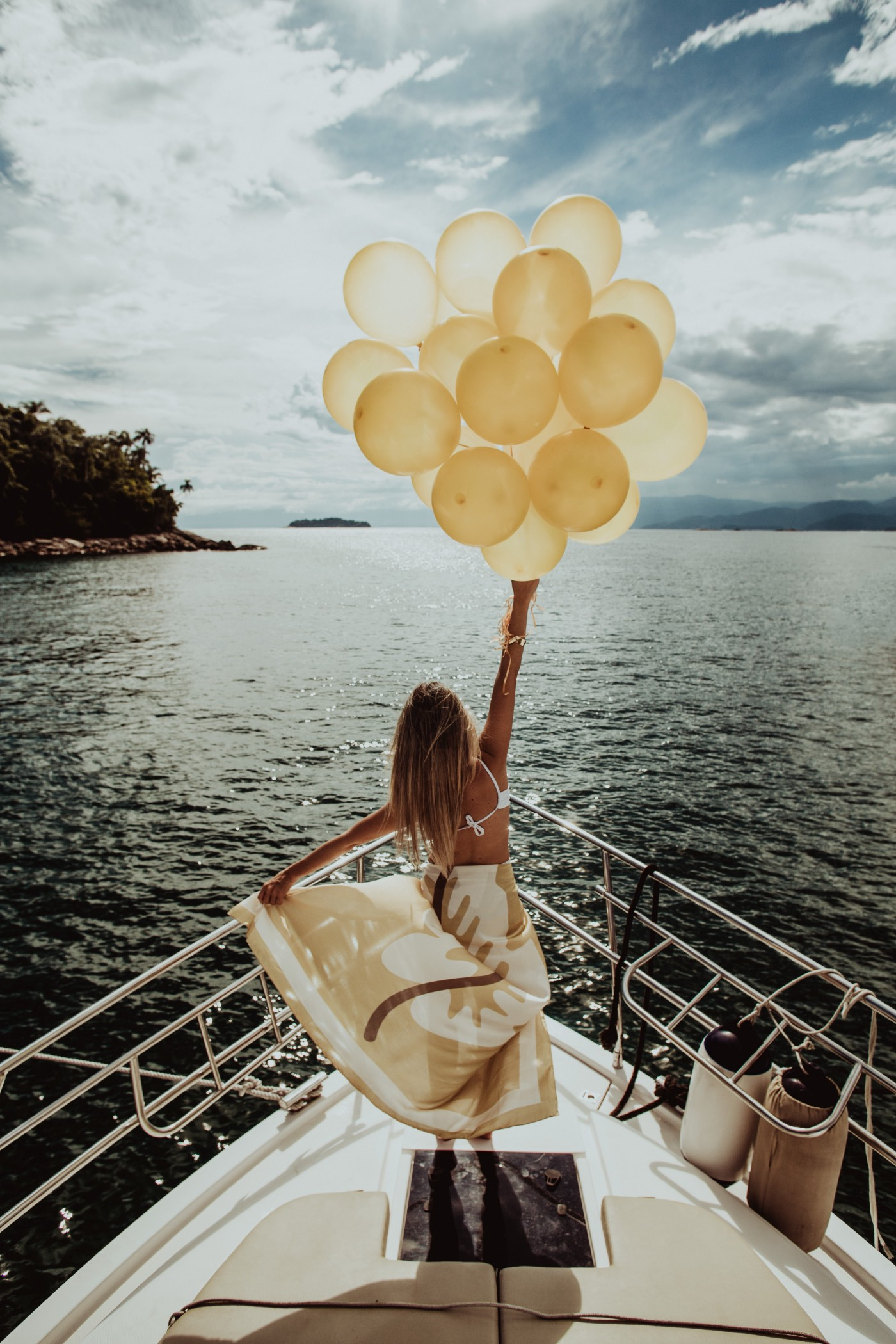 Woman wearing a dress on the bow of a yacht holding a large bouquet of balloons.