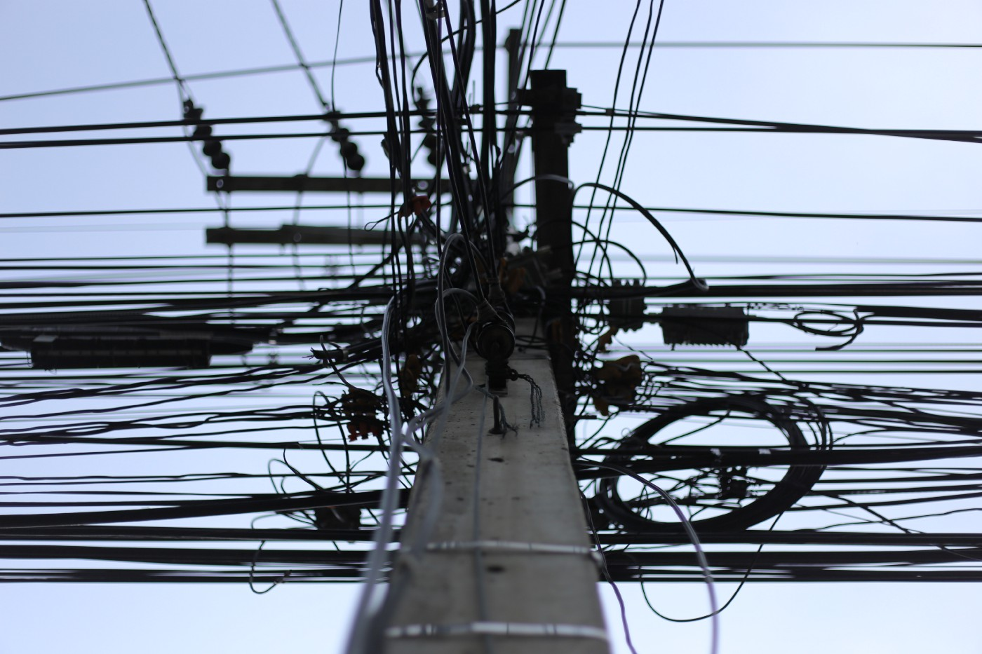 A telephone pole with a massive number of wires attached.