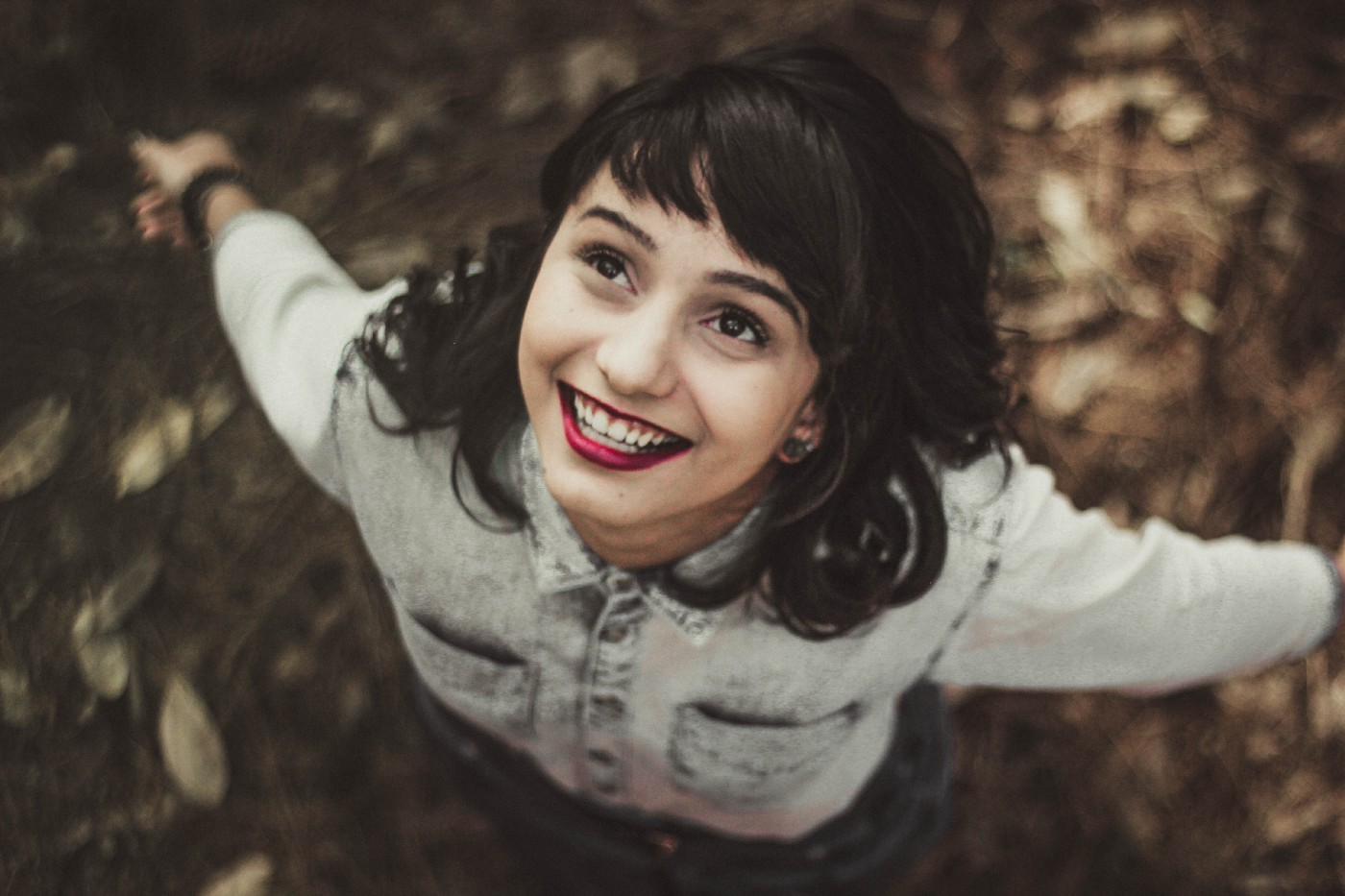 A young woman with short dark brown hair, wearing a bleached denim jacket and dark red lipstick is standing on a bed of brown autumn leaves with her arms outstretched and looking up with a big hopeful smile. I Learned the Value of Love From a Superhero Movie. The silver screen can do wonders for ADHDers like me. What is the true value of love to you? ADHD and love. ADHD and relationships. Value of love.