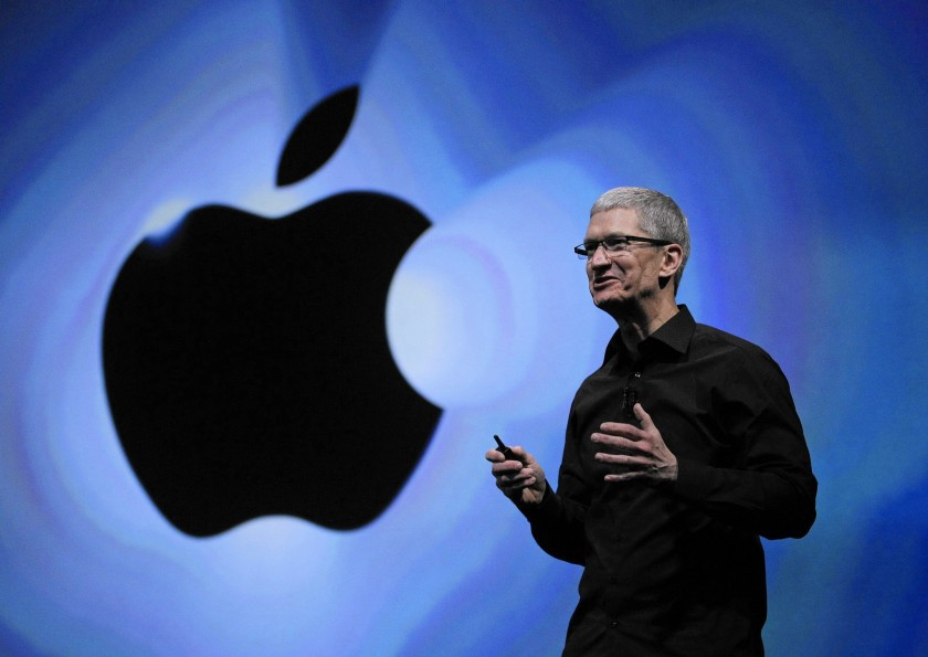 A picture of Apple CEO Tim Cook giving a talk with the Apple logo behind him
