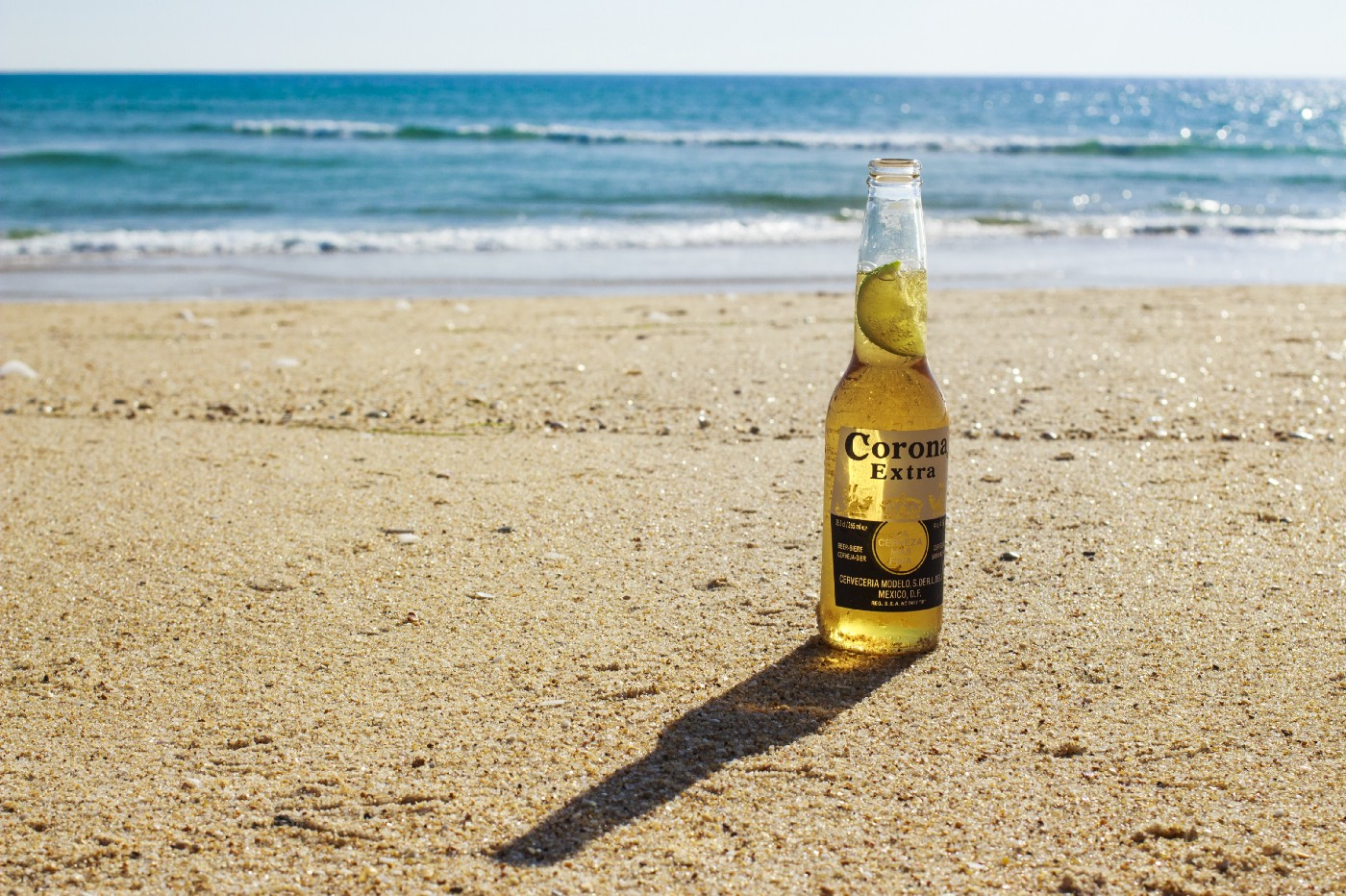 A bottle of Corona Extra with a lime wedge in the neck sits alone on a sandy beach by the water