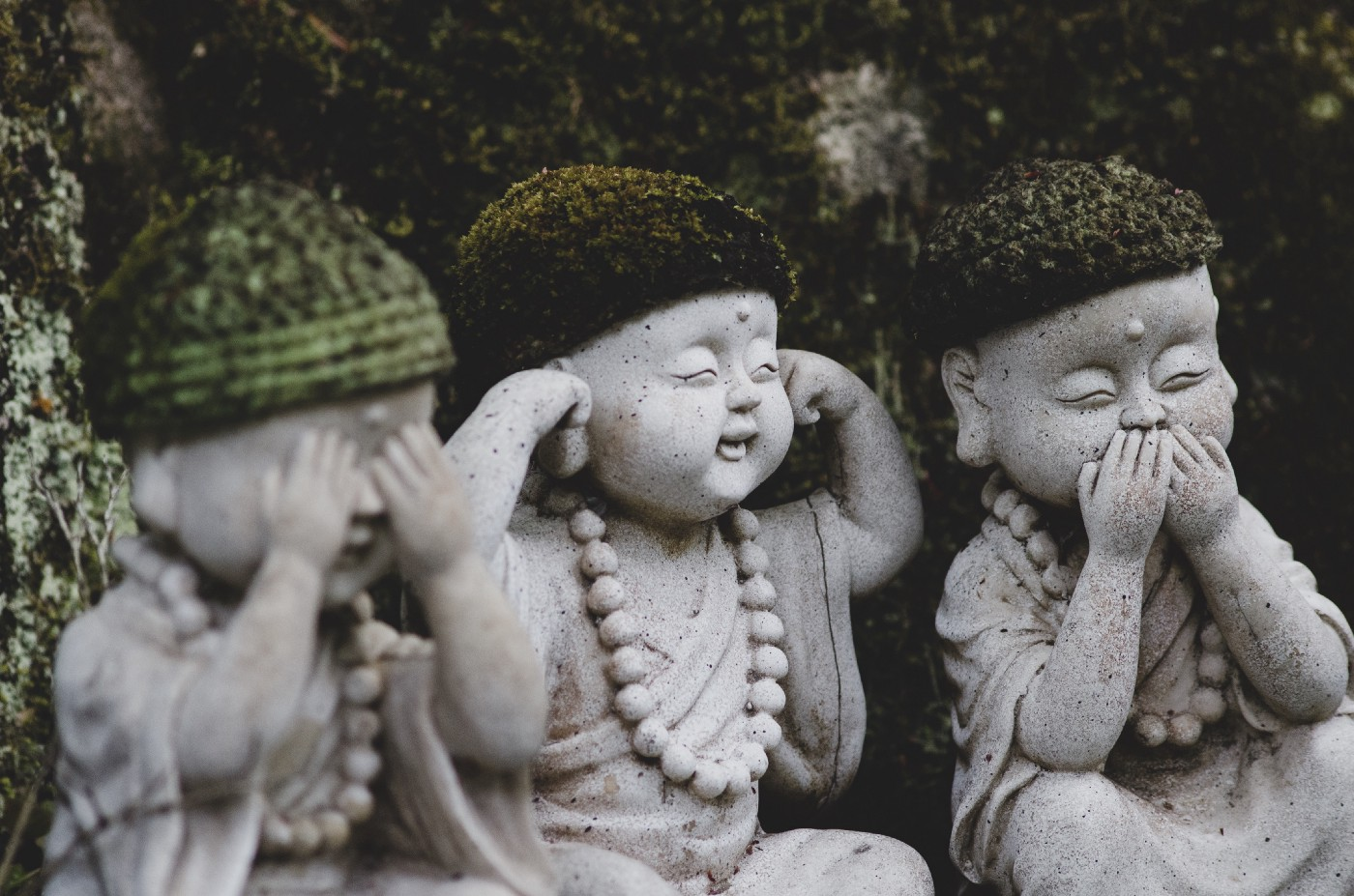 3 stone statues of Buddha-like children. One covers their eyes; one, their ears; and one, their mouth.