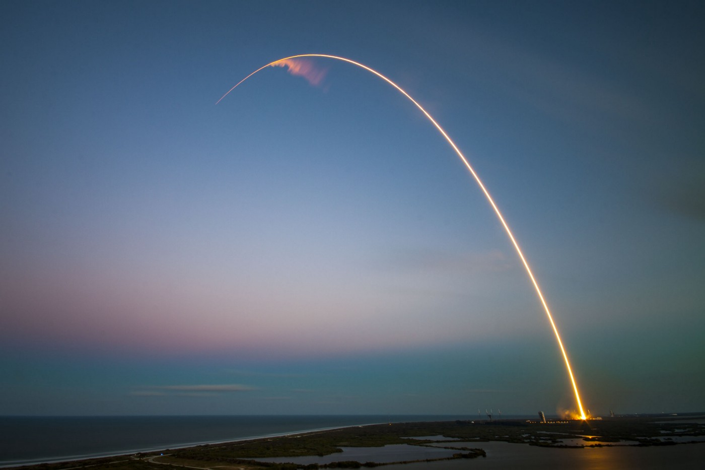 A rocket taking off in a beautiful arch in the evening sky.