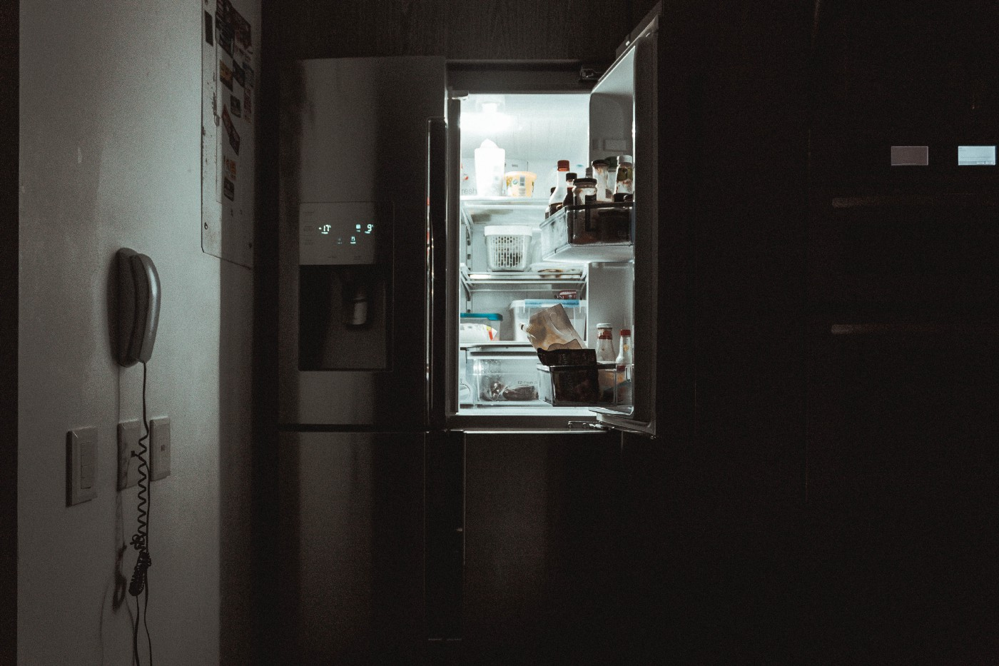 An open, lit refrigerator in a dark kitchen waiting for a fridge forage session to find your next meal.
