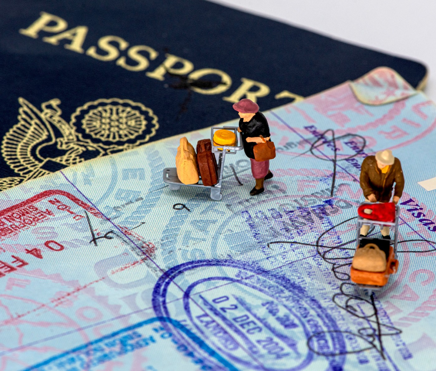 open US passport with miniature figures and entry/exit stamps