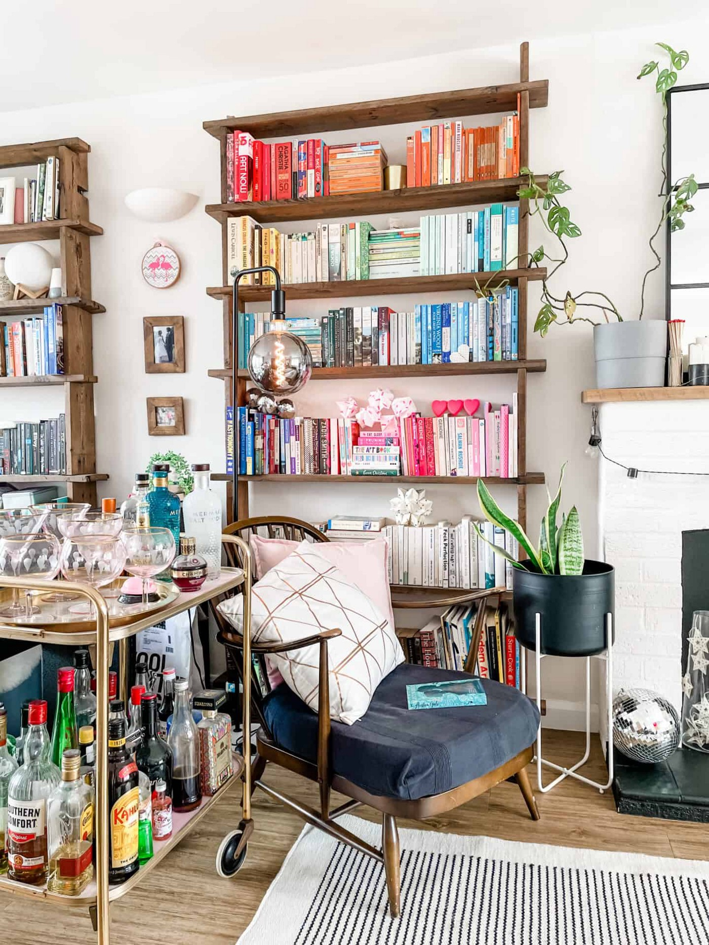 Living room with colour coded bookshelves, a drinks trolley and an Ercol arm chair with an industrial style black floorlamp lit up by a giant LED bulb