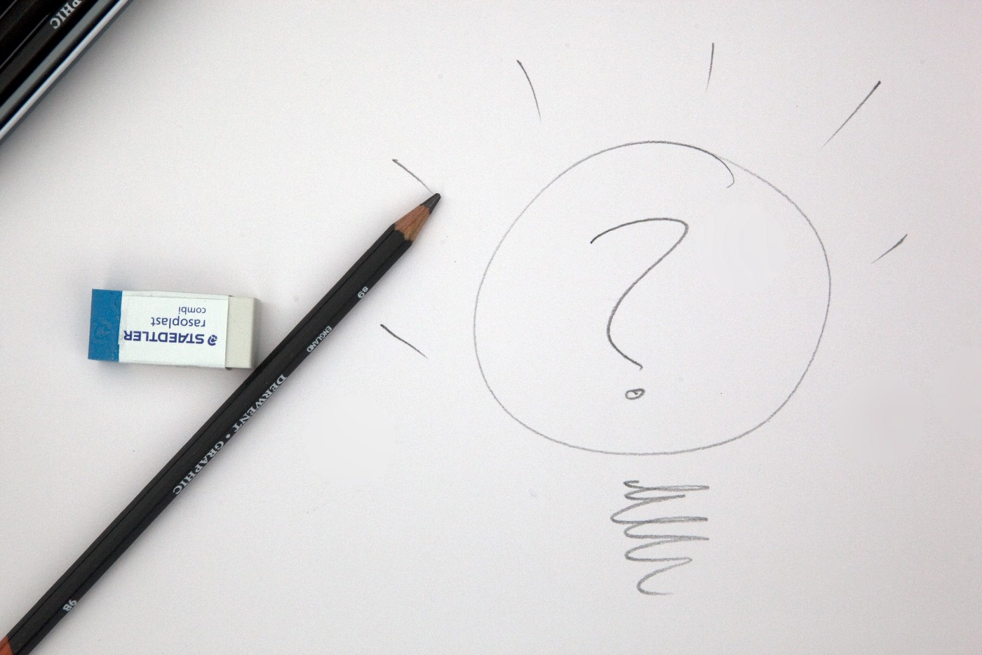 White paper with a pencil drawing of a lightbulb with a question mark inside and rays from the bulb.