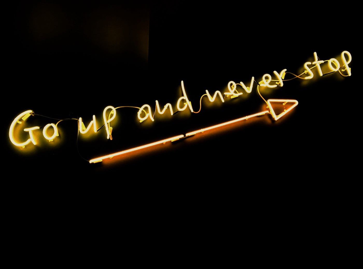 """Neon sign says """"go up and never stop""""."""