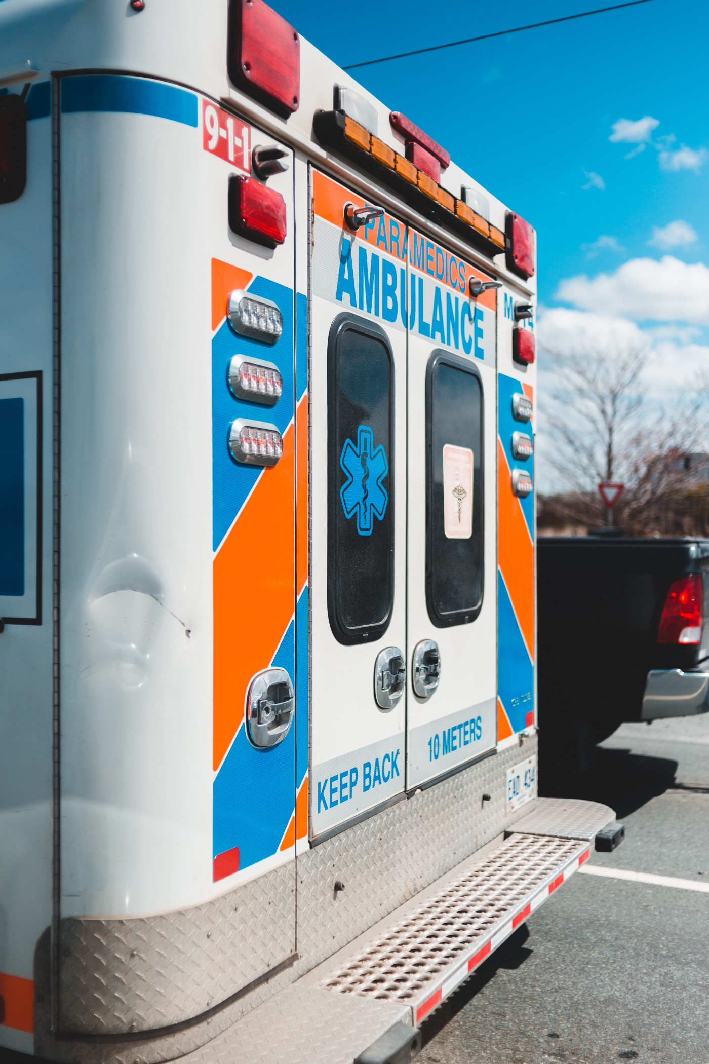 Back end of an ambulance parked on a scene, showing the EMS logo with the caduceus