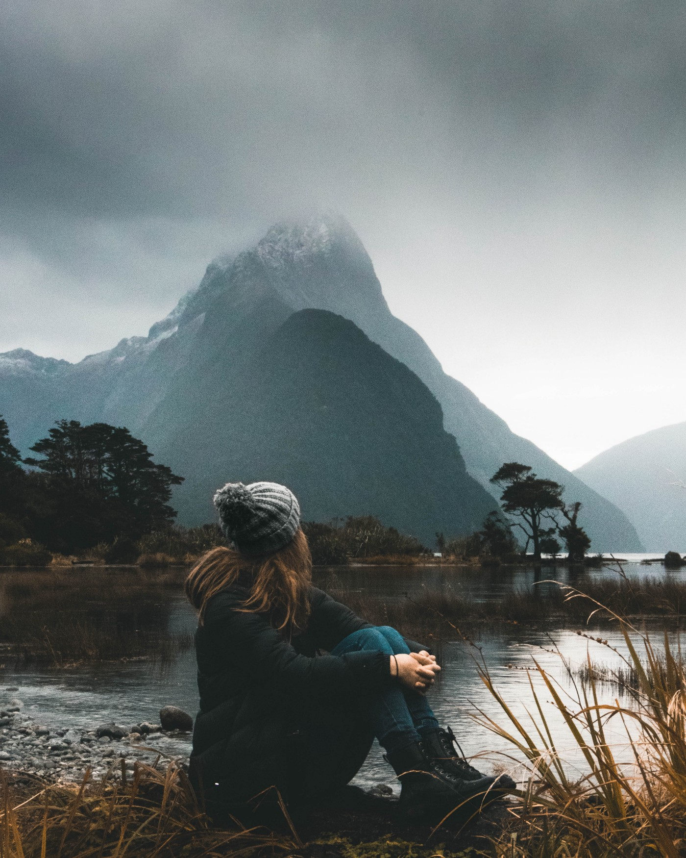girl wearing toque sitting holding her legs looking at mountain across lake