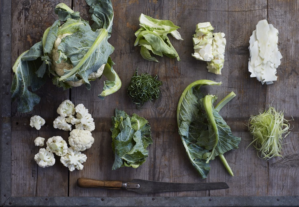 A head of cauliflower next to small piles of cauliflower stems, florets, leaves, stalks, and ribs, respectively.