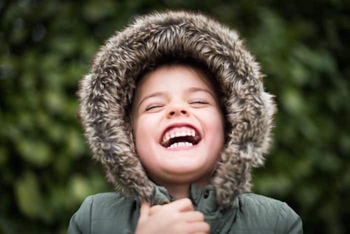 a little girl in a green coat with a huge smile on her face