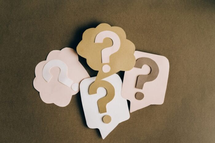 Paper question marks on top of paper speech bubbles