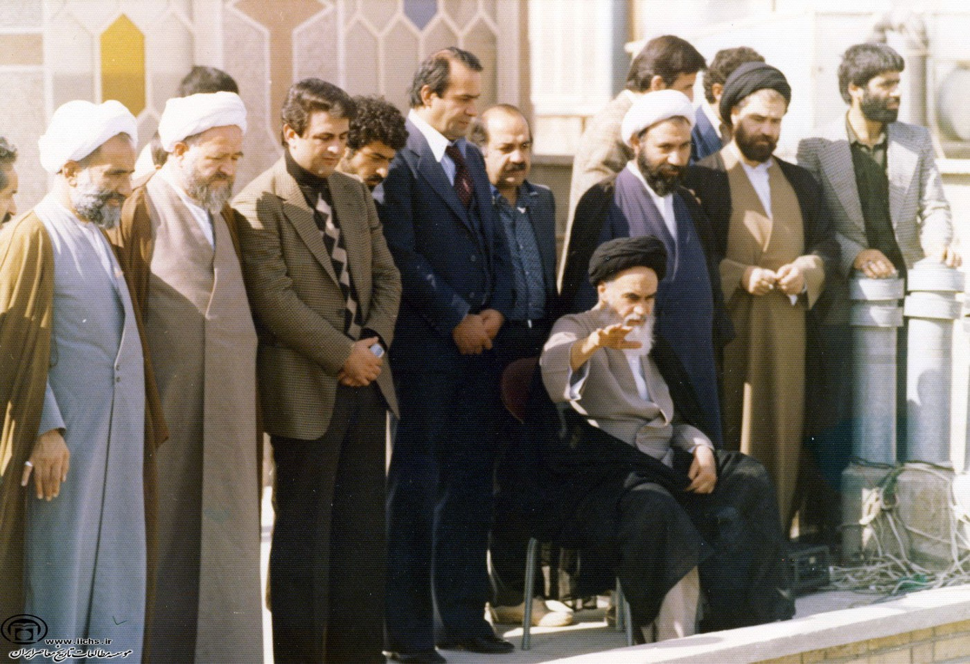 Photo: Unknown photographer. Ruhollah Khomeini on the roof of his residence, Qom. 1979, Wikimedia Commons. https://commons.wi