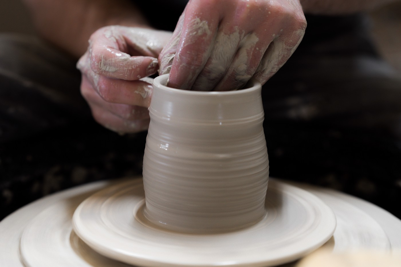 Hands working clay on potters wheel
